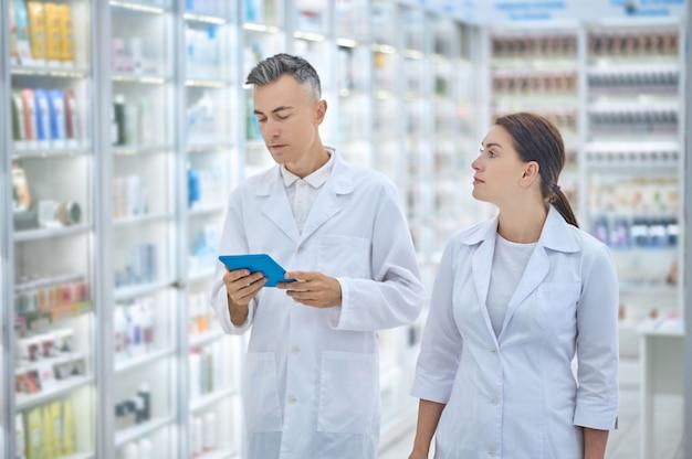 Homem de jaleco branco com tablet e colega