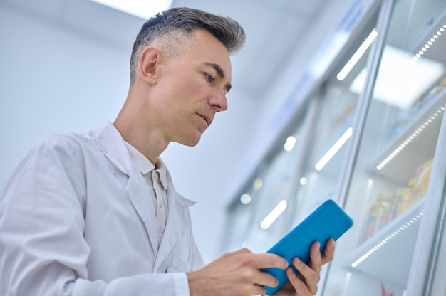 Homem de jaleco olhando atentamente para o tablet