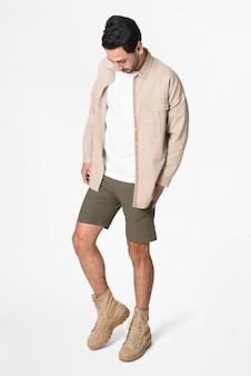 Homem de jaqueta bege e shorts streetwear de corpo inteiro