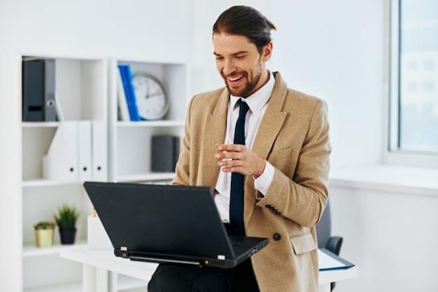 Homem de jaqueta bege no escritório com estilo de vida laptop