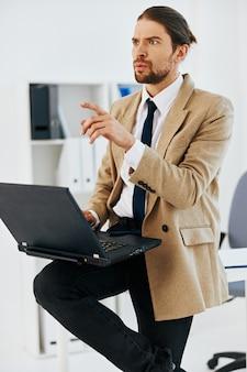 Homem de jaqueta bege no escritório com um executivo com laptop