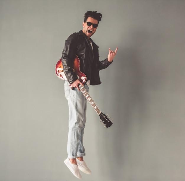 Homem de jaqueta de couro e óculos de sol está segurando uma guitarra