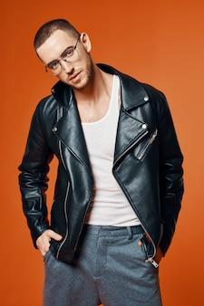 Homem de jaqueta de couro posando moda modelo de fundo laranja