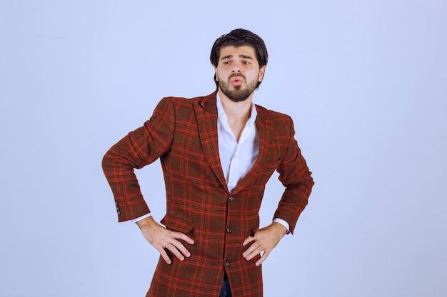 Homem de jaqueta marrom em pé e observando sem reação.