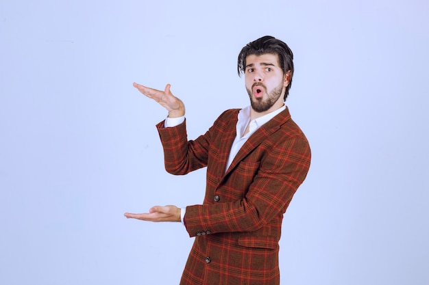 Homem de jaqueta marrom, mostrando as dimensões de um objeto.