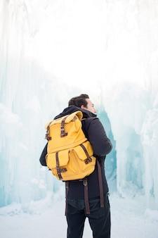 Homem de jaqueta preta e mochila marrom parado na floresta nebulosa