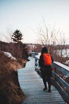 Homem de jaqueta vermelha e preta andando na ponte de madeira durante o dia