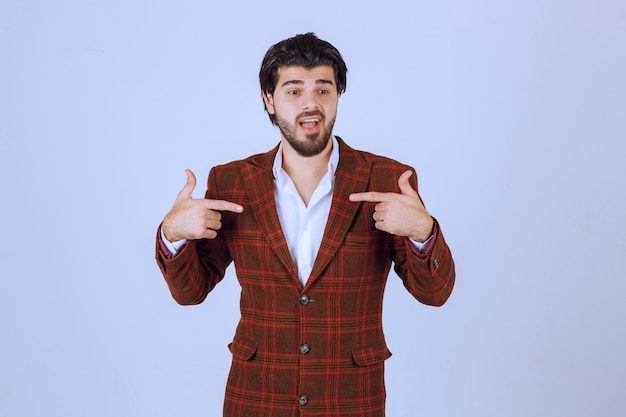 Homem de jaqueta xadrez, apontando a si mesmo e atuando.