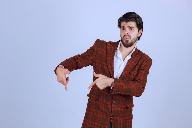 Homem de jaqueta xadrez apontando para baixo com o dedo e mostrando algo.