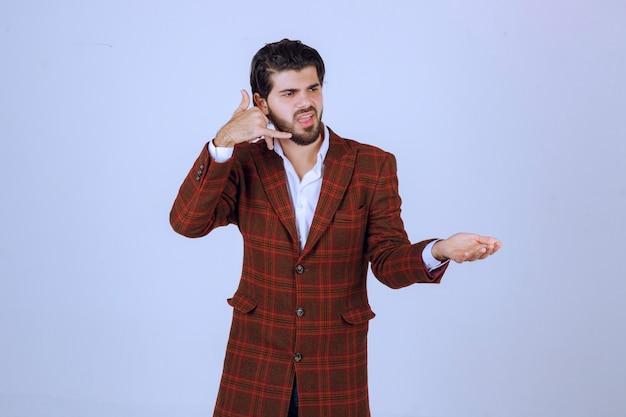 Homem de jaqueta xadrez fazendo indicativo de chamada.