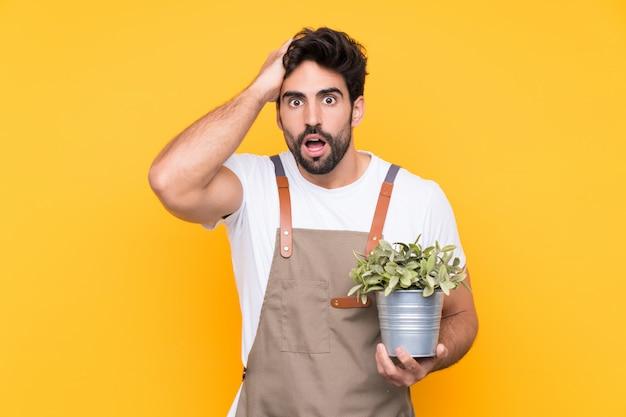 Homem de jardineiro com barba sobre parede amarela isolada com expressão facial de surpresa