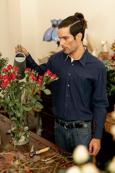 Homem de jardineiro com cabelos longos, regando as plantas