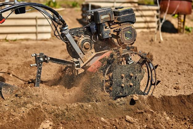 Homem de jardineiro cultivar solo solo com trator de leme ou rototiller, cutivator, máquina de milhagem, prepare-se para o plantio de culturas na primavera.
