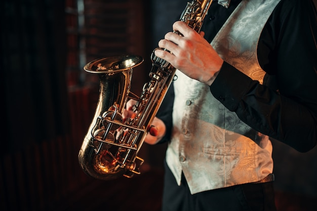 Homem de jazz com mãos segurando saxofone
