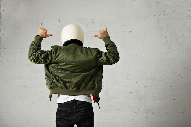 Homem de jeans, camiseta branca, capacete branco de motociclista e jaqueta bomber gesticulando com as mãos, retrato traseiro