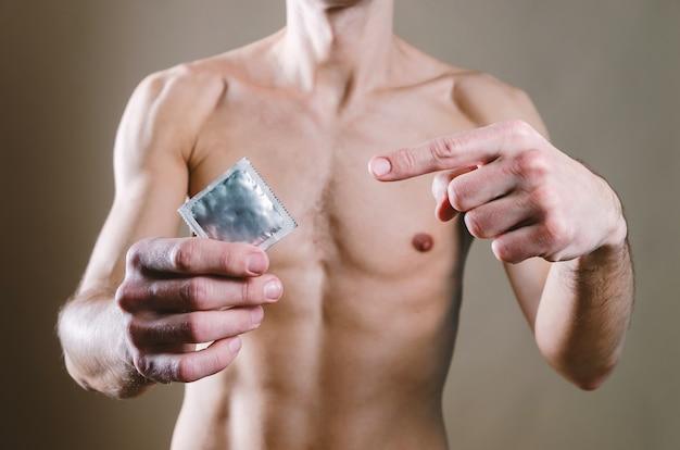 Homem de jeans preto está segurando uma camisinha, enquanto a outra mão está apontando para um contraceptivo com o dedo indicador.