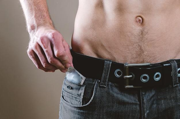 Homem de jeans preto tira uma camisinha do bolso da frente