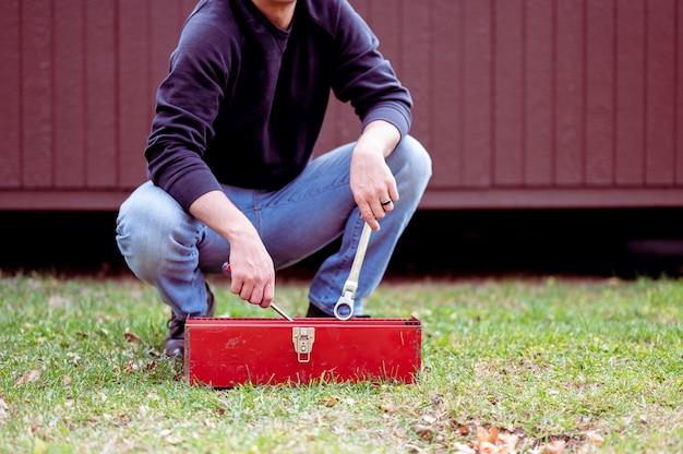 Homem de jeans segurando uma chave inglesa com uma caixa de ferramentas vermelha