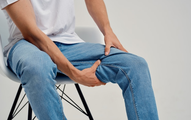 Homem de jeans sentado em uma cadeira e tocando a perna com as mãos