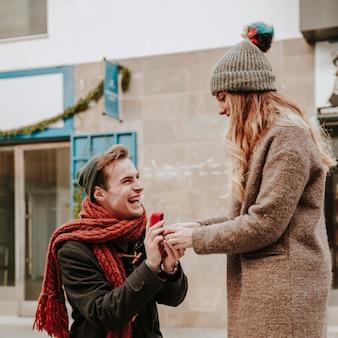Homem de joelho proposto a mulher na rua