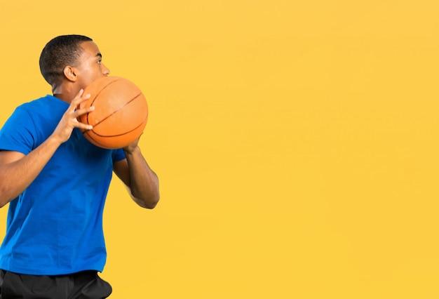 Homem de jogador de basquete afro-americano sobre parede amarela isolada