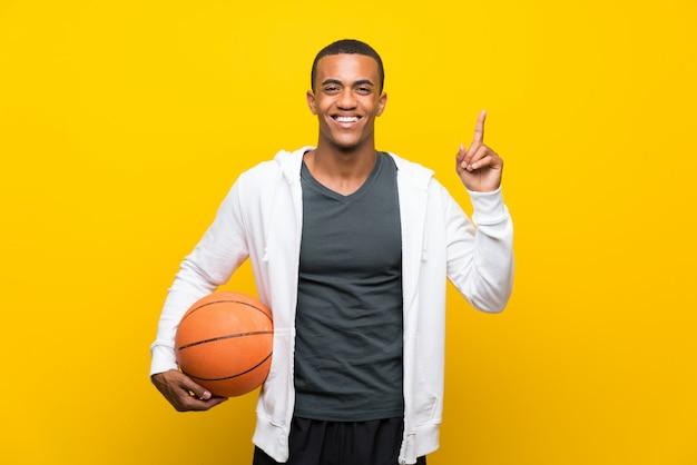 Homem de jogador de basquete americano africano apontando para cima uma ótima idéia
