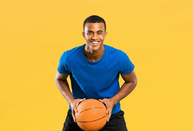 Homem de jogador de basquete americano afro isolado em amarelo