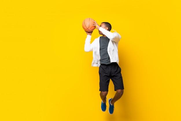 Homem de jogador de basquete americano afro sobre amarelo isolado