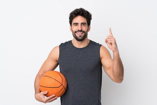Homem de jogador de basquete com barba sobre parede branca isolada, apontando para cima uma ótima idéia