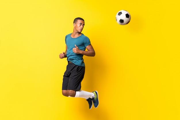 Homem de jogador de futebol afro-americano sobre amarelo isolado