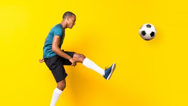 Homem de jogador de futebol afro-americano sobre fundo amarelo isolado