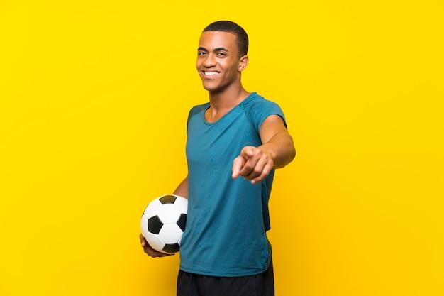 Homem de jogador de futebol americano africano aponta o dedo para você com uma expressão confiante