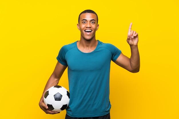 Homem de jogador de futebol americano africano, com a intenção de perceber a solução, levantando um dedo