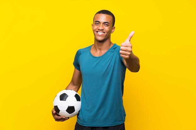 Homem de jogador de futebol americano africano com polegares para cima porque algo de bom aconteceu