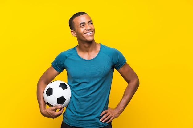 Homem de jogador de futebol americano africano olhando para cima enquanto sorrindo