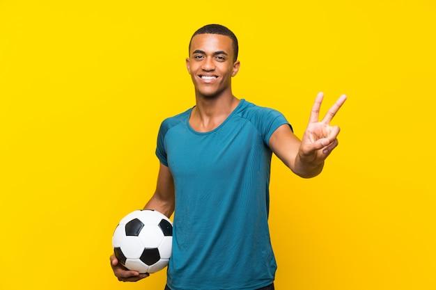 Homem de jogador de futebol americano africano sorrindo e mostrando sinal de vitória