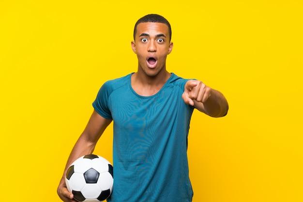 Homem de jogador de futebol americano africano surpreso e apontando a frente