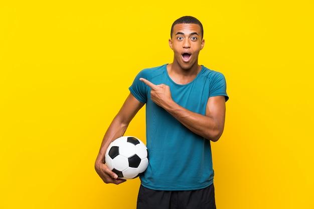 Homem de jogador de futebol americano africano surpreso e apontando o lado