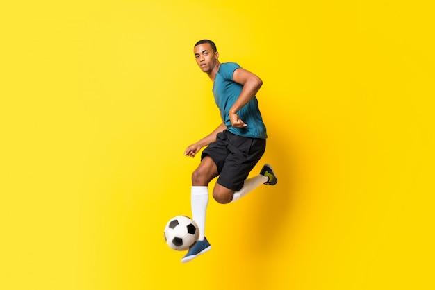 Homem de jogador de futebol americano afro sobre amarelo isolado