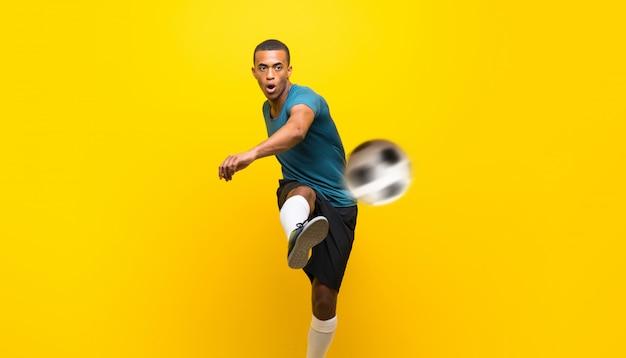Homem de jogador de futebol americano afro sobre fundo amarelo isolado
