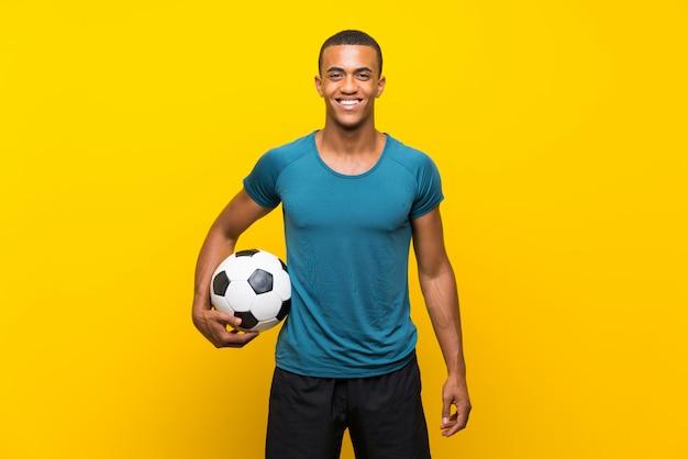 Homem de jogador de futebol americano afro sobre parede amarela isolada