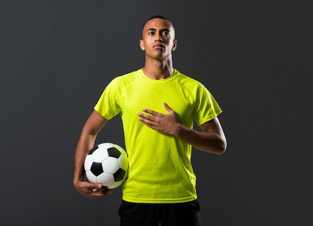 Homem de jogador de futebol com pele escura jogando pegando uma bola com as mãos e cantando o nacional