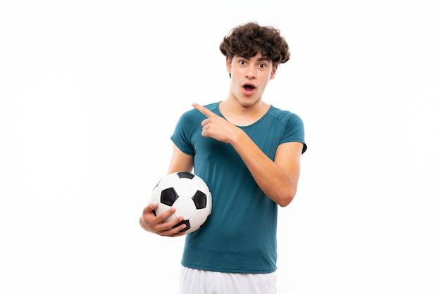 Homem de jogador de futebol jovem sobre parede branca isolada surpreso e apontando o lado
