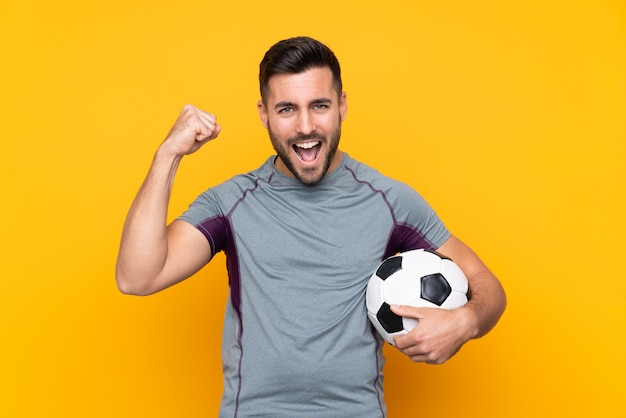 Homem de jogador de futebol sobre parede isolada, comemorando uma vitória