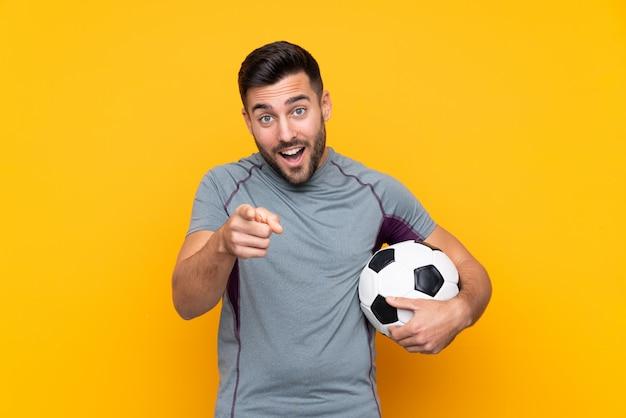 Homem de jogador de futebol sobre parede isolada surpreso e apontando a frente