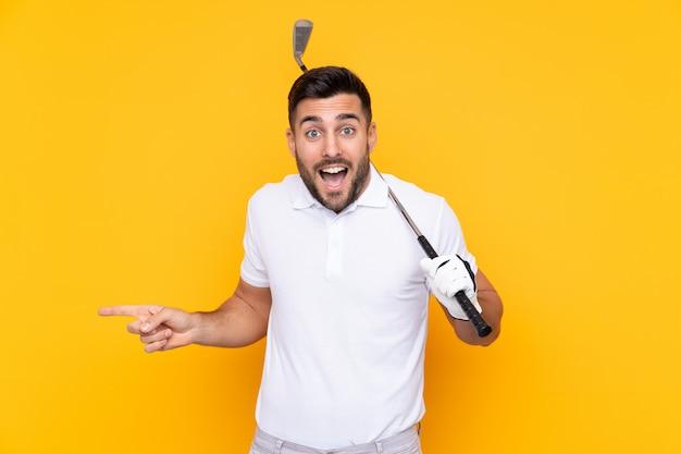 Homem de jogador de golfe isolado parede amarela surpreso e apontando o lado