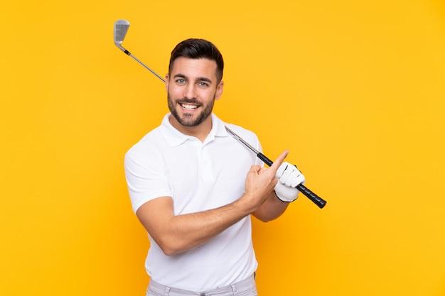 Homem de jogador de golfe sobre parede amarela isolada, apontando para o lado para apresentar um produto