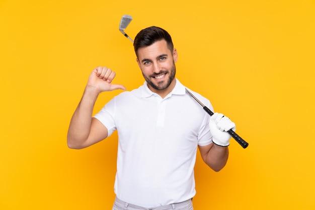Homem de jogador de golfe sobre parede amarela isolada, orgulhoso e satisfeito