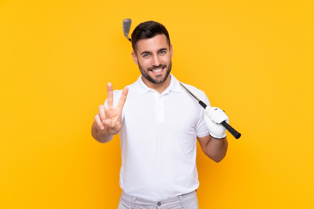 Homem de jogador de golfe sobre parede amarela isolada, sorrindo e mostrando sinal de vitória