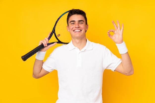 Homem de jogador de tênis adolescente bonito isolado em fundo amarelo, jogando tênis e fazendo sinal de ok